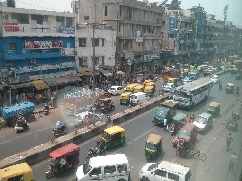 Liikennettä Delhissä. Myös tällä tiellä riitti väärään suuntaan menijöitä, rullaluistelija ja tien ylittäjiä uhkarohkeista pieniin koululaisiin. Bussin takaosan yllä näkyyhevoskärryt.